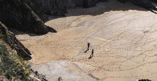 2 personnes marchent sur le sable avec des traces de pas